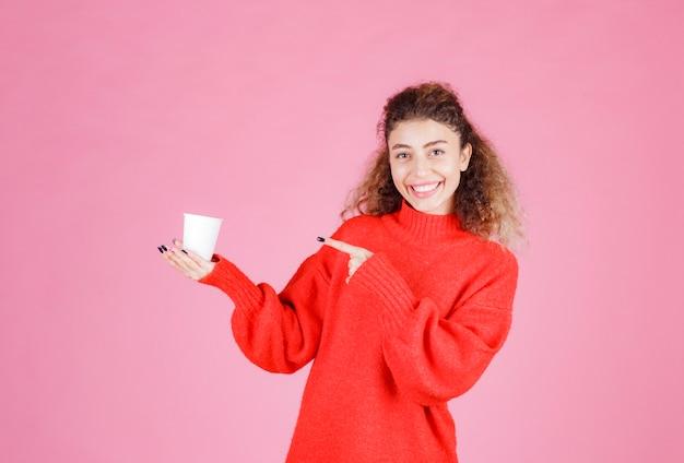 Vrouw in rood shirt met een wegwerp koffiekopje.