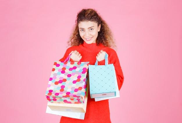 Vrouw in rood shirt met meerdere kleurrijke boodschappentassen.
