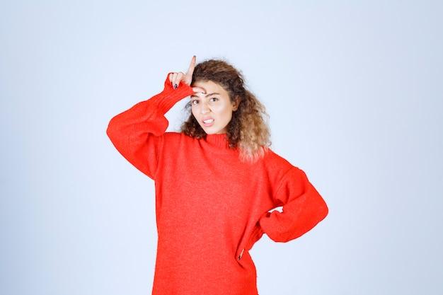 Vrouw in rood shirt met verliezer handteken.