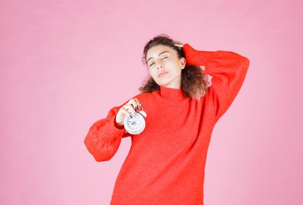 Vrouw in rood shirt met wekker en ziet er slaperig uit.