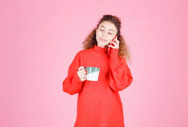 Vrouw in rood shirt praten met de telefoon tijdens het drinken van koffie.