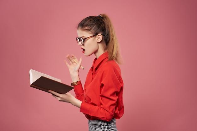 Vrouw in rood shirt secretaresse werk mode roze achtergrond. hoge kwaliteit foto
