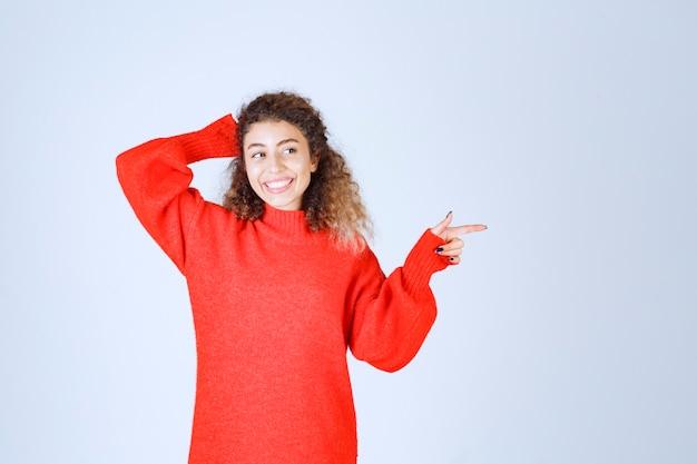 Vrouw in rood shirt wijzend naar iemand of ergens met een emotioneel gezicht op blauw.