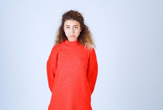 Vrouw in rood sweatshirt die neutrale poses geeft.