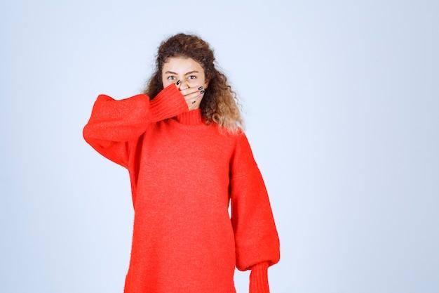 Vrouw in rood sweatshirt die over haar vingers kijkt.