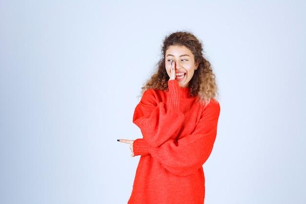 Vrouw in rood sweatshirt die vrolijke en positieve poses geeft.