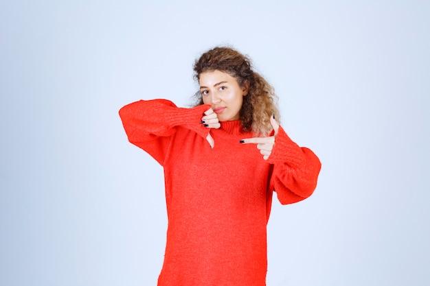 Vrouw in rood sweatshirt met duim omlaag teken.