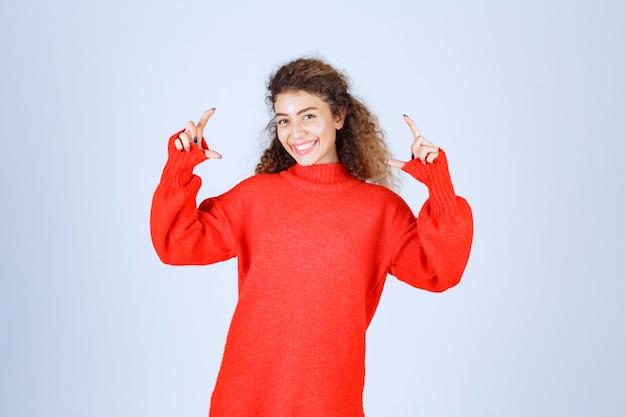 Vrouw in rood sweatshirt showint de afmetingen van een object.