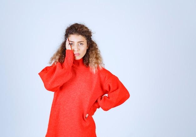 Vrouw in rood sweatshirt ziet er doodsbang en bang uit.