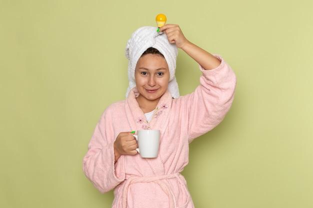 Vrouw in roze badjas glimlachend en thee drinken