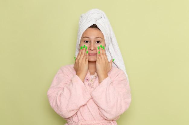 Vrouw in roze badjas haar gezicht wrijven met room