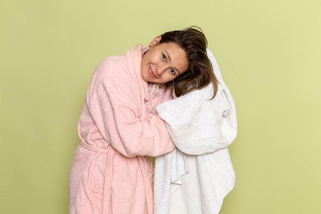 Vrouw in roze badjas haar haren drogen