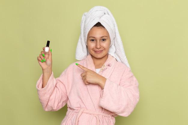 Vrouw in roze badjas met nagellak
