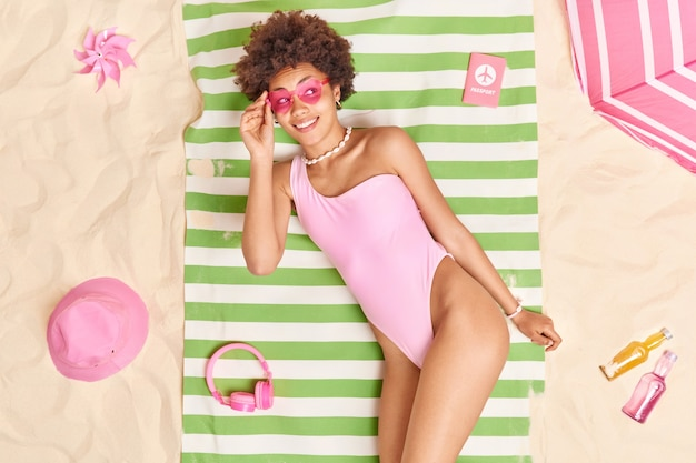 Vrouw in roze bikini hartvormige zonnebril poses op handdoek aan zandstrand omringd door verschillende dingen glimlacht gelukkig geconcentreerd weg. zomertijd en rustconcept