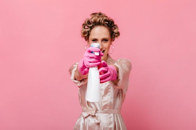 Vrouw in roze gewaad en handschoenen stuurt spiegelreiniger naar voren