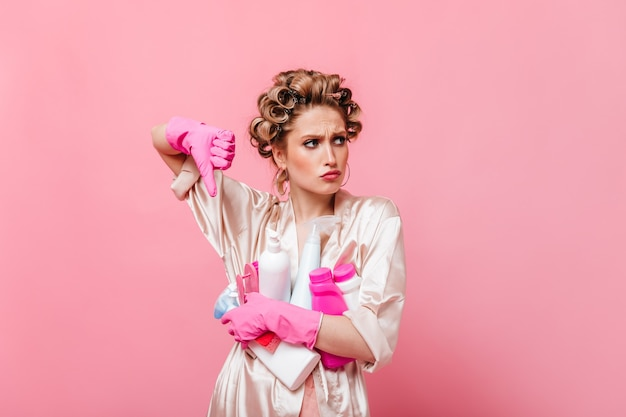 Vrouw in roze gewaad toont vinger naar beneden en houdt wasmiddel op geïsoleerde muur