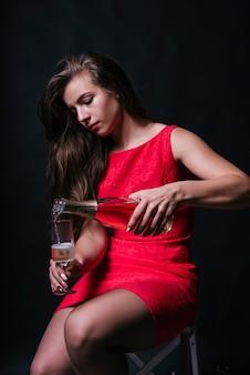 Vrouw in roze gieten champagne in glas