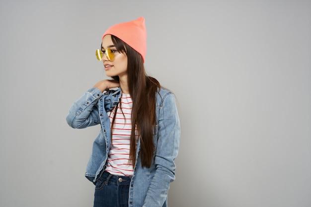 Vrouw in roze hoed gele bril studio grijze achtergrond mode