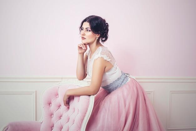 Vrouw in roze interieur en roze lange jurk als een prinses