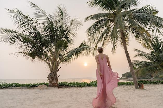 Vrouw in roze jurk genieten van prachtige zonsondergang op het strand
