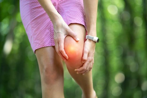 Vrouw in roze jurk met haar knie met handen kramp pijn.