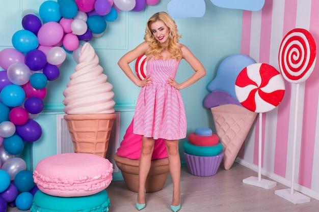 Vrouw in roze jurk op achtergrond versierd met enorme snoepjes en ijs