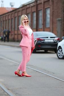 Vrouw in roze kostuum en met paraplu die de weg kruist