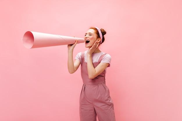 Vrouw in roze outfit aan haar oor vastgemaakt enorm stuk papier in buis gerold.