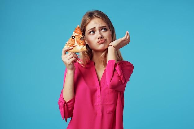 Vrouw in roze overhemdpizza die snel voedseldieet blauwe achtergrond houdt
