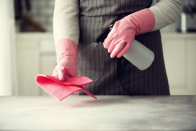 Vrouw in roze rubber beschermende handschoenen die stof en vuil afvegen.