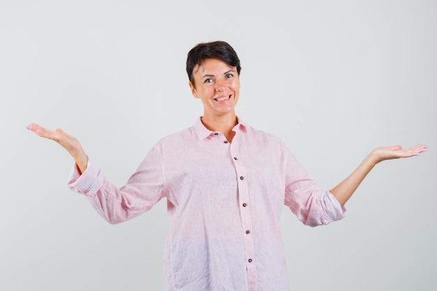 Vrouw in roze shirt dat iets presenteert of vergelijkt en er vrolijk uitziet, vooraanzicht.