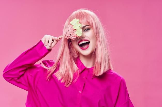 Vrouw in roze shirt met snoepmodel pop