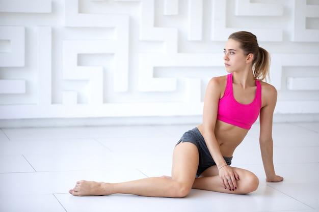 Vrouw in roze sportkleding ontspant op de vloer na een training. studio opname.