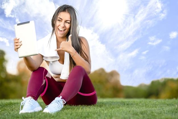 Vrouw in roze yoga broek met een witte handdoek om haar nek een selfie te nemen op een met gras begroeide heuvel