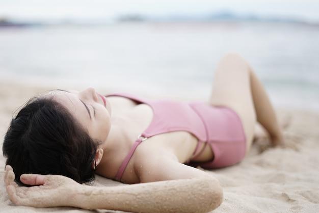 Vrouw in roze zwempak die op het zandige strand liggen