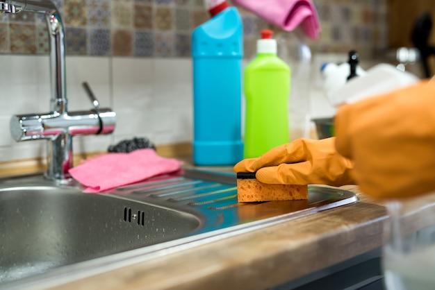 Vrouw in rubberen handschoenen die vuil oppervlak in de keuken schoonmaken. huiswerk