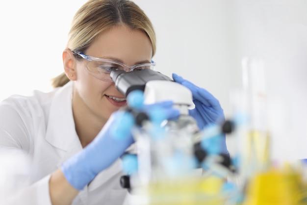 Vrouw in rubberen handschoenen en beschermende chemische bril kijkt door microscoop in laboratoriumportret. het concept van klinische diagnostische analyses uitvoeren.