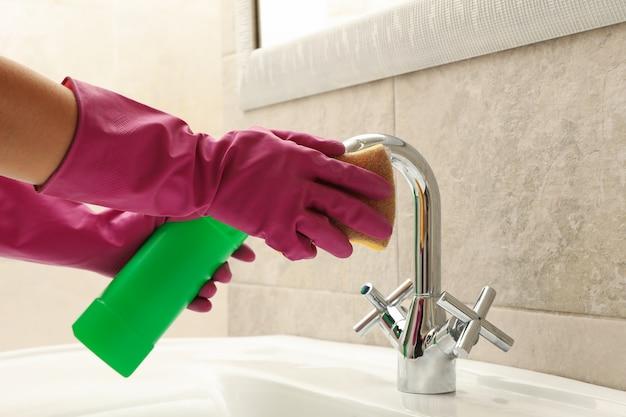 Vrouw in rubberen roze handschoen schoonmaak gootsteen