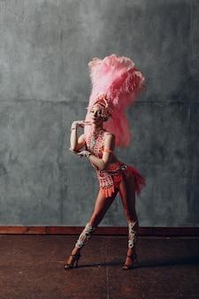 Vrouw in samba of lambadakostuum met roze verenkleed.