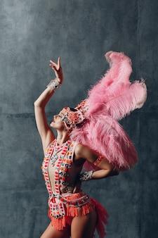 Vrouw in samba of lambadakostuum met roze verenkleed