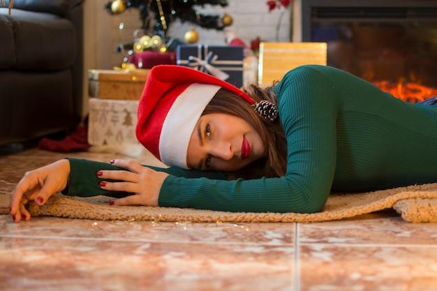 Vrouw in santa claus-hoed, die op de vloer van haar huis met kerstmisdecoratie liggen