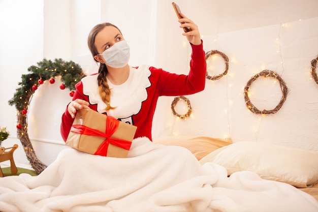 Vrouw in santa claus jacket houdt telefoon vast en communiceert met haar vrienden in beschermende maskers. externe viering van nieuwjaar en kerstmis