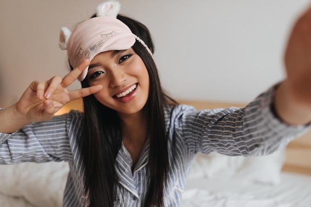 Vrouw in schattig slaapmasker vertoont teken van vrede en maakt selfie in de slaapkamer