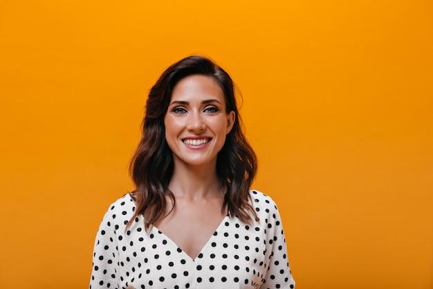Vrouw in schattige blouse lacht op oranje achtergrond