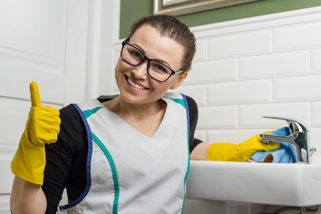 Vrouw in schoonmaak kleren geven duimen omhoog