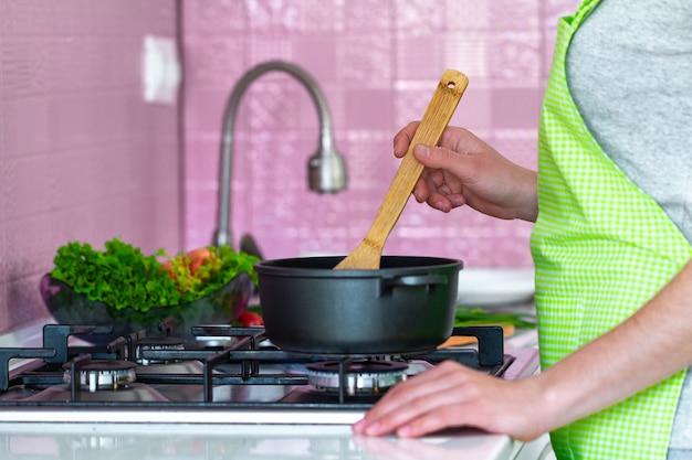 Vrouw in schort die dichtbij fornuis en kokende soep zich bij keuken zich thuis bevinden. koken voorbereiding voor het gezin voor het avondeten. schoon gezond voedsel en goede voeding.