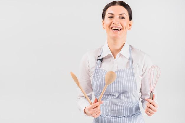 Vrouw in schort die en werktuig glimlachen houden