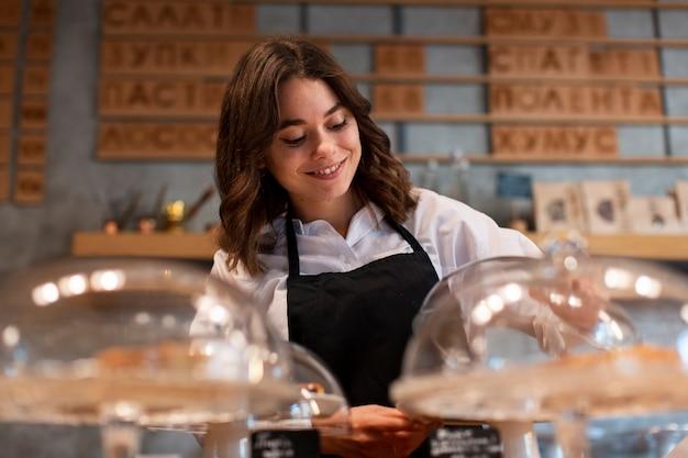 Vrouw in schort die in koffiewinkel werkt