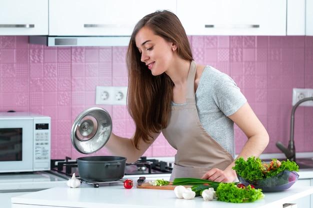 Vrouw in schort kokend diner van verse rijpe groenten thuis. schoon eten en een gezonde levensstijl