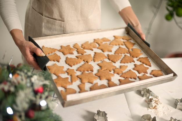 Vrouw in schort met bakplaat lade met gemberkoekjes van kerstmis